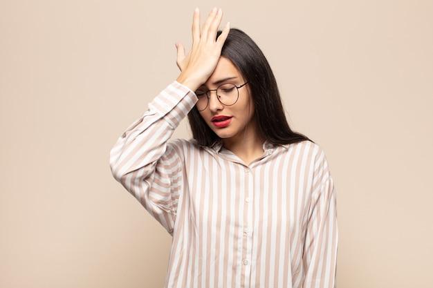 Giovane donna ispanica alzando il palmo alla fronte pensando oops, dopo aver commesso uno stupido errore o ricordando, sentendosi stupido