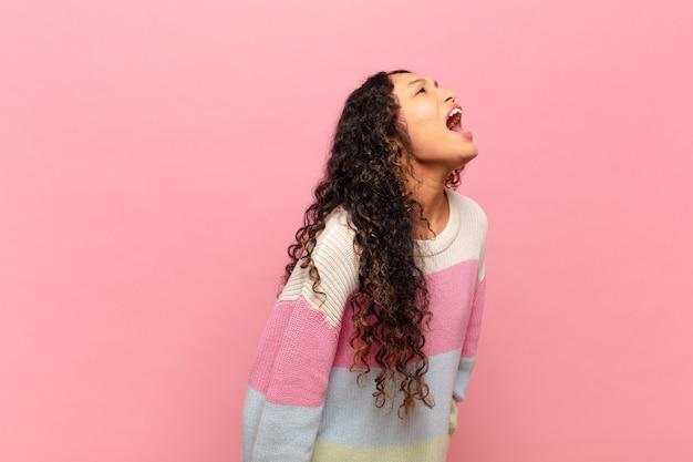 Giovane donna ispanica che urla furiosamente, urla in modo aggressivo, sembra stressata e arrabbiata