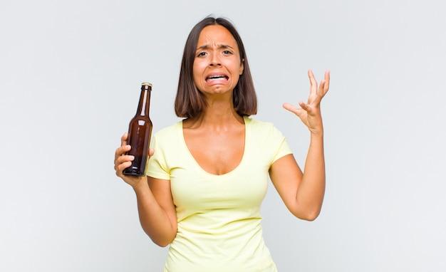 Giovane donna ispanica che grida con le mani in aria, sentendosi furiosa, frustrata, stressata e sconvolta
