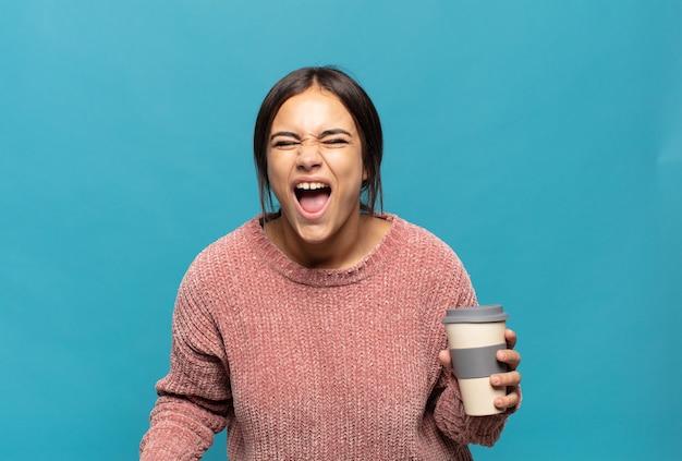 Giovane donna ispanica che grida in modo aggressivo, sembra molto arrabbiata, frustrata, oltraggiata o infastidita, grida di no
