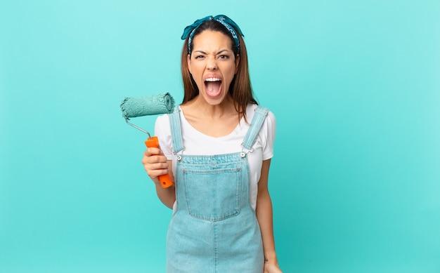 Giovane donna ispanica che grida in modo aggressivo, sembra molto arrabbiata e dipinge un muro
