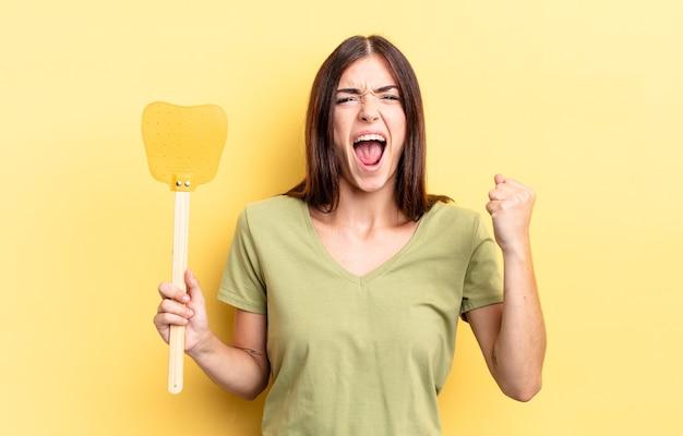 Giovane donna ispanica che grida in modo aggressivo con un'espressione arrabbiata. uccidere mosche concetto