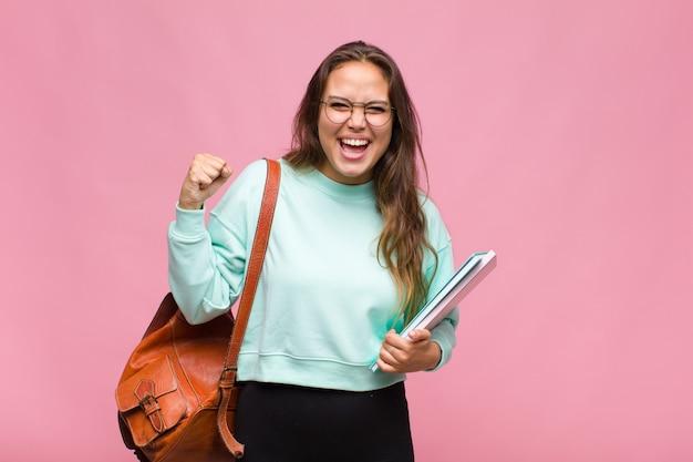 Giovane donna ispanica che grida in modo aggressivo con un'espressione arrabbiata o con i pugni chiusi per celebrare il successo