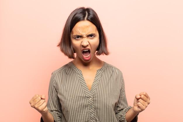 Giovane donna ispanica che grida in modo aggressivo con un'espressione arrabbiata o con i pugni chiusi celebrando il successo