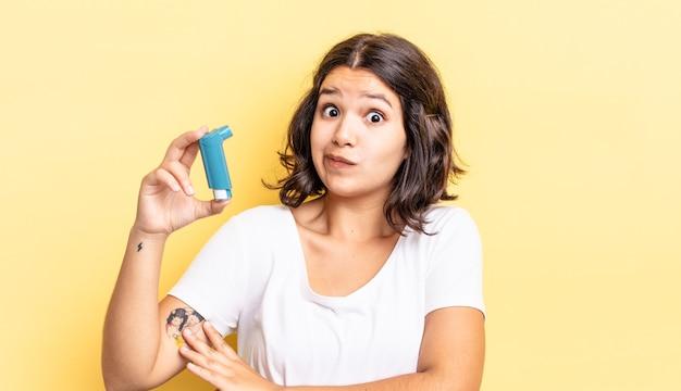 Giovane donna ispanica che scrolla le spalle, sentendosi confusa e incerta. concetto di asma