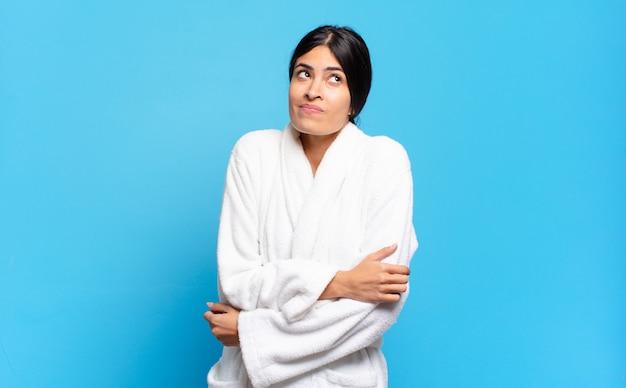 Giovane donna ispanica che scrolla le spalle, si sente confusa e incerta, dubitando con le braccia incrociate e lo sguardo perplesso. concetto di accappatoio