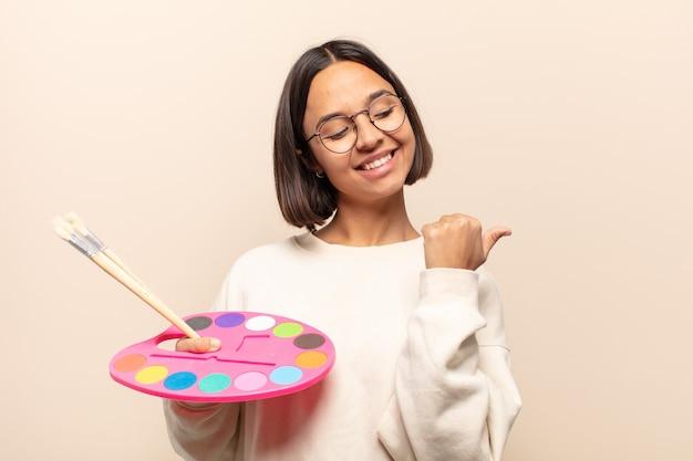 Giovane donna ispanica che sorride allegramente e casualmente indicando lo spazio di copia sul lato, sentendosi felice e soddisfatta