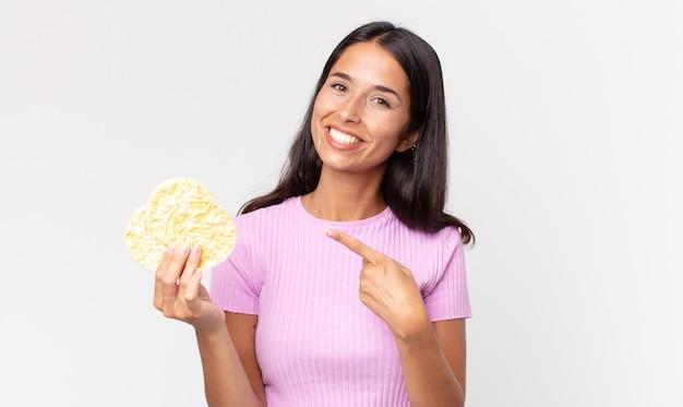 Giovane donna ispanica che sorride allegramente, si sente felice e indica il lato e tiene in mano un biscotto di riso. concetto di dieta