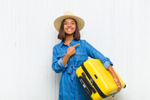 Giovane donna ispanica che sorride allegramente, sentendosi felice e indicando il lato e verso l'alto, mostrando l'oggetto nello spazio della copia