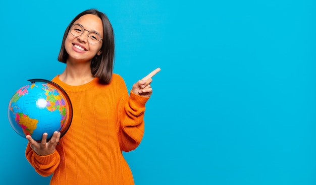 Giovane donna ispanica che sorride allegramente, si sente felice e indica di lato e verso l'alto, mostrando l'oggetto nello spazio della copia