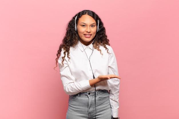 Giovane donna ispanica che sorride allegramente, sentendosi felice e mostrando un concetto nello spazio della copia con il palmo della mano. concetto di telemarketer