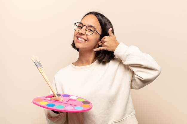 Giovane donna ispanica sorridendo allegramente e indicando mentre si effettua una chiamata in seguito gesto, parlando al telefono