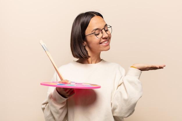 Giovane donna ispanica che sorride, sentendosi sicura, di successo e felice, mostrando il concetto o l'idea sullo spazio della copia sul lato