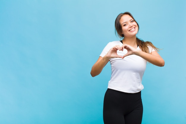 Giovane donna ispanica sorridente e sentirsi felice, carina, romantica e innamorata, facendo forma di cuore con entrambe le mani