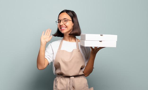 Giovane donna ispanica che sorride allegramente e allegramente, agitando la mano, dandoti il benvenuto e salutandoti o salutandoti