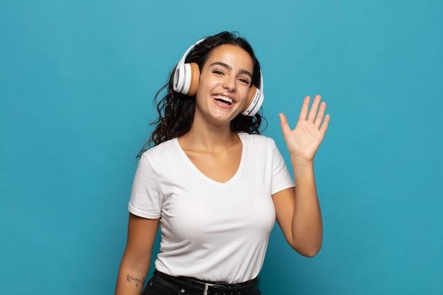 Giovane donna ispanica che sorride allegramente e allegramente, agitando la mano, accogliendoti e salutandoti o salutandoti