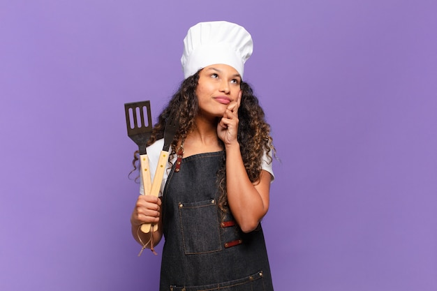 Giovane donna ispanica che sorride felicemente e sogna ad occhi aperti o dubita, guardando di lato. concetto di chef barbecue