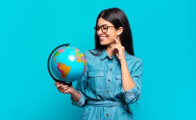 Giovane donna ispanica sorridente felicemente e fantasticando o dubitando, guardando al lato. concetto di pianeta terra
