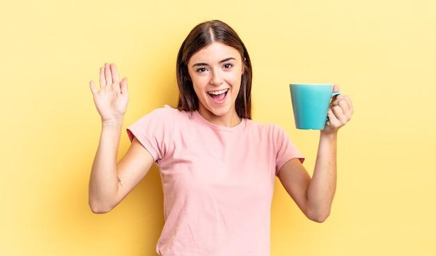 Giovane donna ispanica che sorride felicemente, agitando la mano, accogliendoti e salutandoti. concetto di tazza di caffè