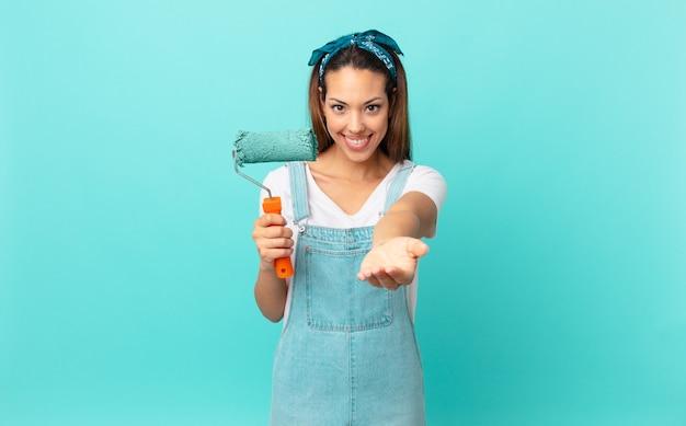 Giovane donna ispanica che sorride felicemente con amichevole e offrendo e mostrando un concetto e dipingendo un muro