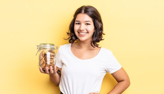 Giovane donna ispanica che sorride felicemente con una mano sull'anca e fiduciosa. concetto di bottiglia di biscotti