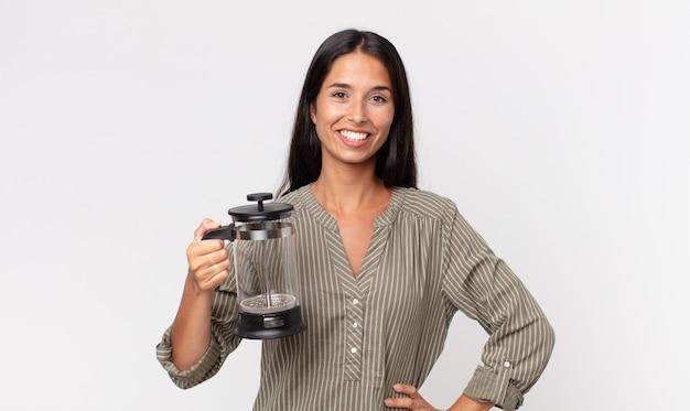 Giovane donna ispanica che sorride felicemente con una mano sull'anca e sicura e tiene in mano una caffettiera manuale