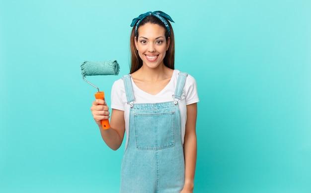 Giovane donna ispanica che sorride felicemente con una mano sull'anca e sicura e dipinge un muro