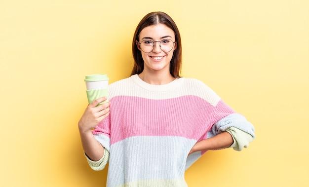 Giovane donna ispanica che sorride felicemente con una mano sull'anca e sicura di sé. portare via il concetto di caffè