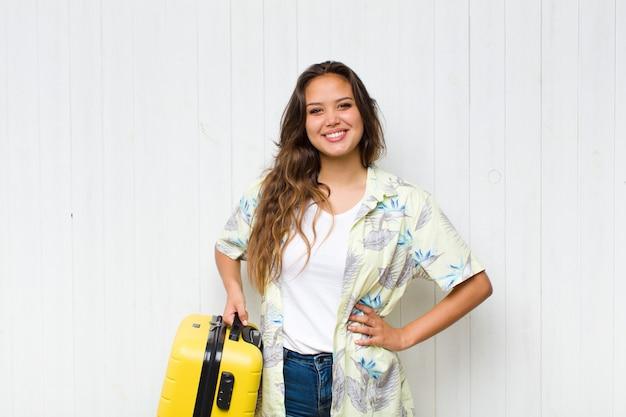 Giovane donna ispanica che sorride felicemente con una mano sull'anca e sicura