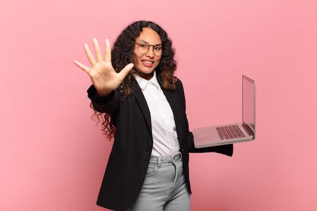 Giovane donna ispanica sorridente e dall'aspetto amichevole, mostrando il numero cinque o il quinto con la mano in avanti, conto alla rovescia. concetto di laptop