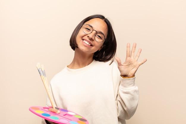Giovane donna ispanica sorridente e dall'aspetto amichevole, mostrando il numero cinque o quinto con la mano in avanti, conto alla rovescia