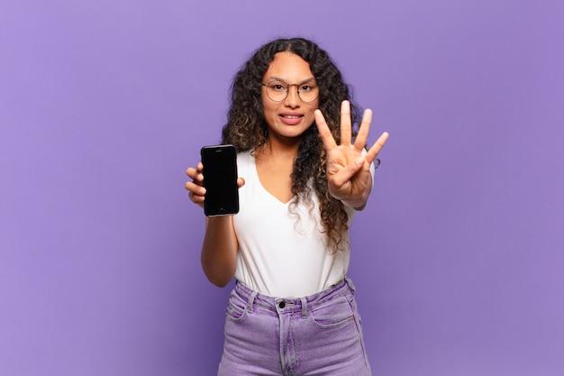 Giovane donna ispanica che sorride e che sembra amichevole, mostrando il numero quattro o il quarto con la mano in avanti, conto alla rovescia. concetto di smart phone