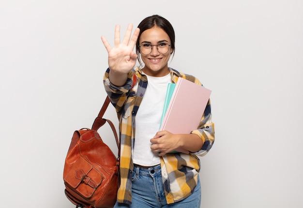 Giovane donna ispanica sorridente e dall'aspetto amichevole, mostrando il numero quattro o quarto con la mano in avanti, il conto alla rovescia
