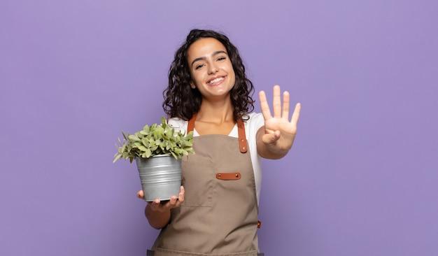 Giovane donna ispanica sorridente e dall'aspetto amichevole, mostrando il numero quattro o il quarto con la mano in avanti, conto alla rovescia