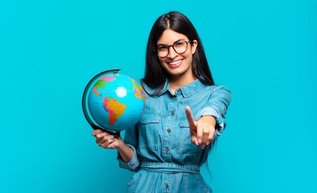 Giovane donna ispanica che sorride e sembra amichevole, mostrando il numero uno o il primo con la mano in avanti, il conto alla rovescia. concetto di pianeta terra