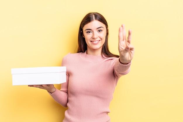 Giovane donna ispanica che sorride e che sembra amichevole, mostrando il numero tre. concetto di scatola vuota