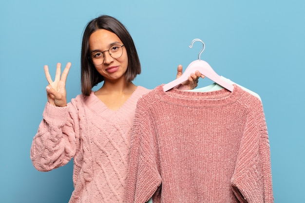 Giovane donna ispanica che sorride e sembra amichevole, mostrando il numero tre o terzo con la mano in avanti, conto alla rovescia