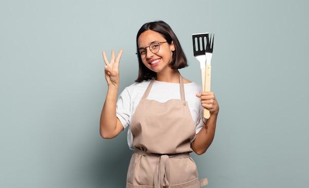Giovane donna ispanica sorridente e dall'aspetto amichevole, mostrando il numero tre o terzo con la mano in avanti, il conto alla rovescia