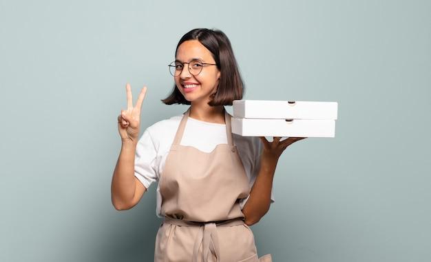 Giovane donna ispanica che sorride e sembra amichevole, mostrando il numero due o il secondo con la mano in avanti, conto alla rovescia