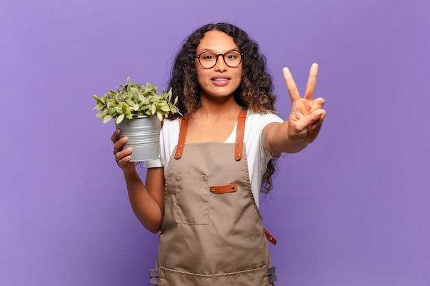 Giovane donna ispanica che sorride e sembra amichevole, mostrando il numero due o il secondo con la mano in avanti