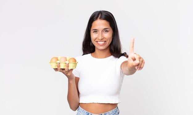 Giovane donna ispanica che sorride con orgoglio e sicurezza facendo il numero uno e tenendo in mano una scatola di uova