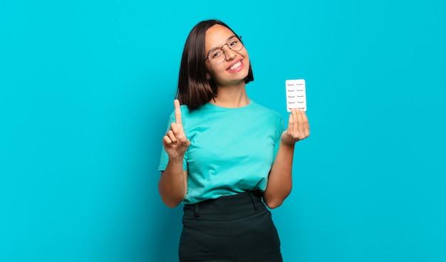 Giovane donna ispanica che sorride con orgoglio e sicurezza facendo posare trionfante il numero uno, sentendosi come un leader