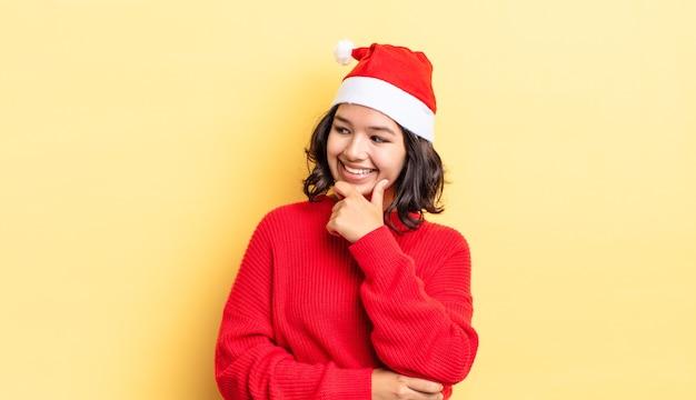 Giovane donna ispanica che sorride con un'espressione felice e sicura con la mano sul mento. concetto di natale