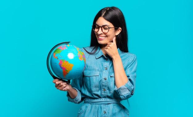 Giovane donna ispanica che sorride con un'espressione felice e sicura con la mano sul mento, chiedendosi e guardando di lato. concetto di pianeta terra
