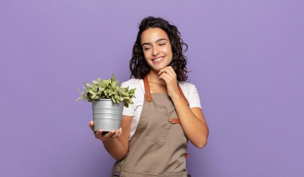 Giovane donna ispanica che sorride con un'espressione felice e sicura con la mano sul mento, chiedendosi e guardando di lato
