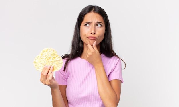 Giovane donna ispanica che pensa, si sente dubbiosa e confusa e tiene in mano un biscotto di riso. concetto di dieta