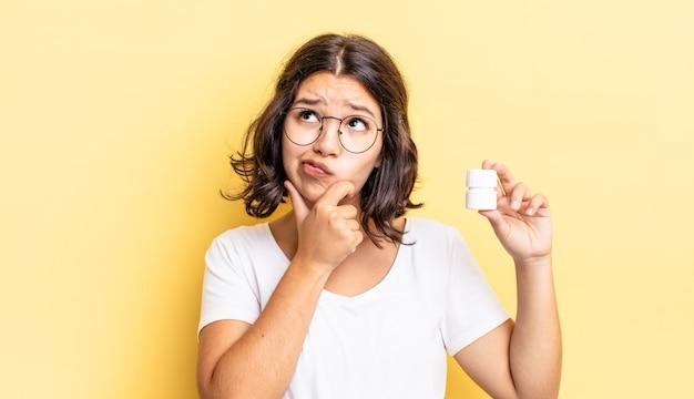 Giovane donna ispanica che pensa, si sente dubbiosa e confusa. concetto di pillole di malattia
