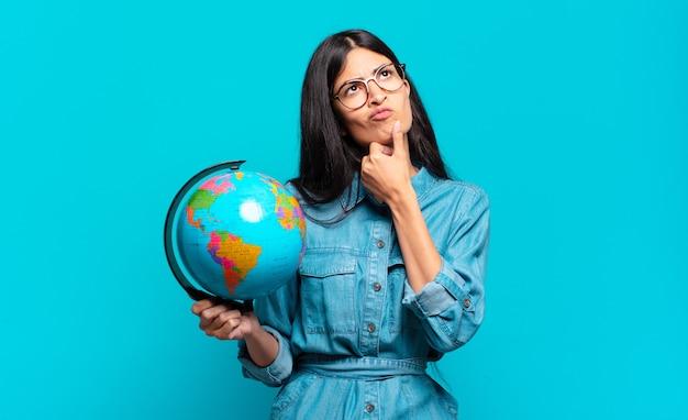 Giovane donna ispanica che pensa, si sente dubbiosa e confusa, con diverse opzioni, chiedendosi quale decisione prendere. concetto di pianeta terra