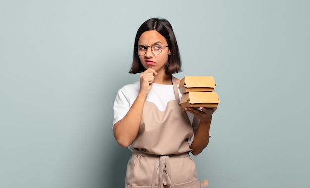 Giovane donna ispanica che pensa, si sente dubbiosa e confusa, con diverse opzioni, chiedendosi quale decisione prendere