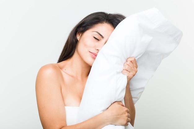 Giovane donna ispanica svegliarsi e tenendo un cuscino